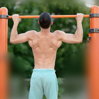 shirtless man working out using a bar at the park