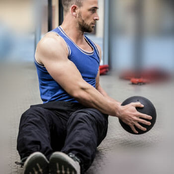 man in a tank top working out his core with a medicine ball