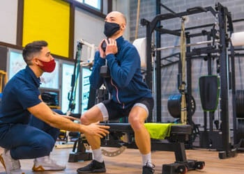 instructor teaching a man how to squat in a gym