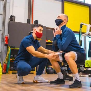 coach teaching a man how to squats