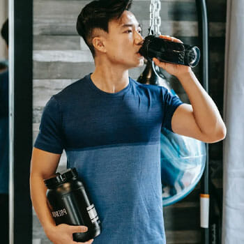 asian man in a gym drinking a supplement from a jug