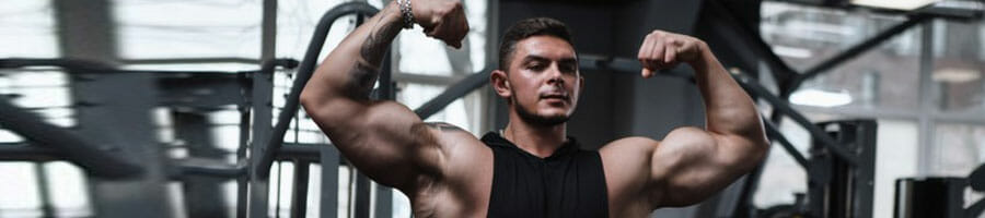 buff man showing of his big biceps in a gym