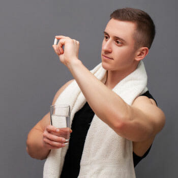 man in gym clothes holding up a piece of pill and a glass of water