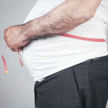 man using a measuring tape on his bloated stomach