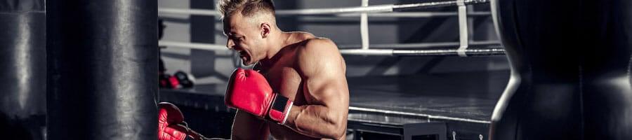 shirtless man using a punching bag