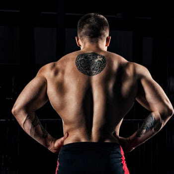 shirtless man with tattoos flexing his back muscles