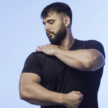 man in a black shirt touching and looking at his shoulder