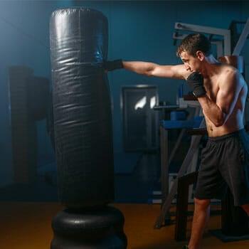 shirtless man punching a standing heavy bag