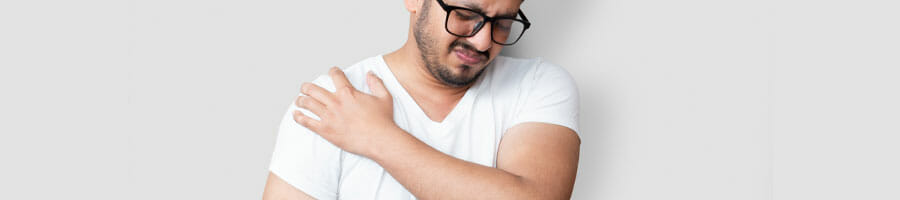 man in a white shirt holding his painful shoulder