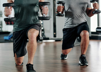 two men doing lunges while holding a dumbbell