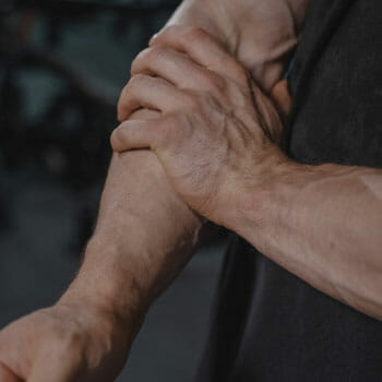 man holding his painful forearm