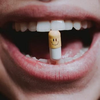 woman holding a pill with her teeth