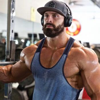 bradley martyn wearing a blue muscle top working out inside a gym