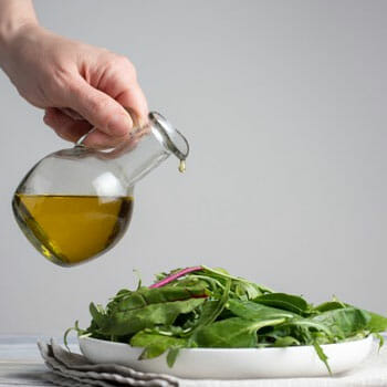leafy salad bowl getting drizzled by olive oil