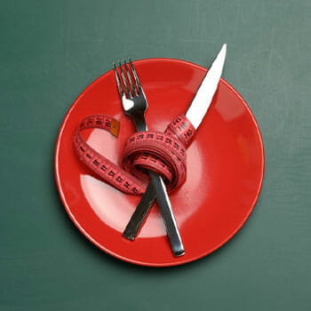 red plate with a measuring tape tied fork and knife