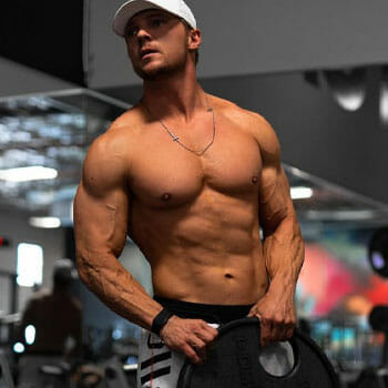 shirtless Steve Cook carrying a barbell plate