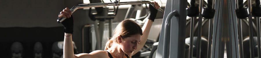 woman frustrated using a lat machine