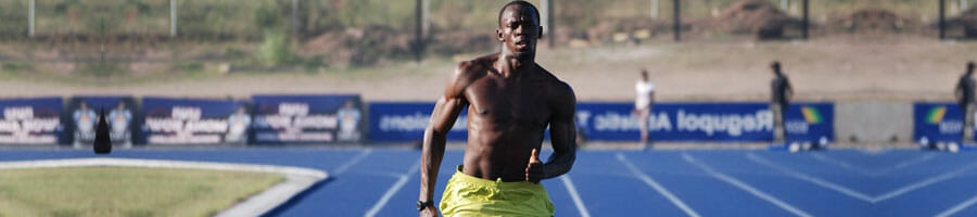 shirtless usain bolt jogging in a field