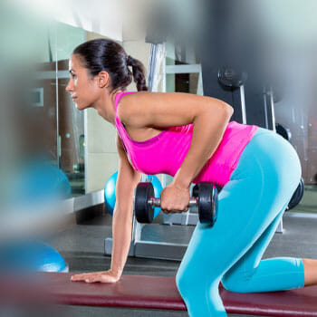 woman wearing gym clothes in a bent over row position