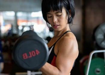 asian woman lifting dumbbells