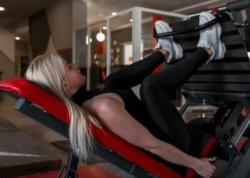 woman using a leg press machine in a gym