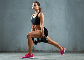 woman in a lunge position holding dumbbells