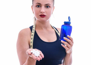 blonde woman holding a jug of water and pills with a measuring tape around her neck