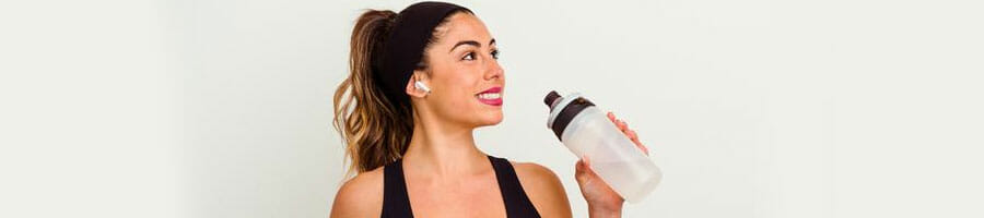 woman smiling while holding a jug of water