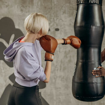 woman wearing a boxing gloves while punching a heavy bag