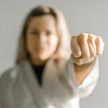 blonde female in a judo uniform showing her fist