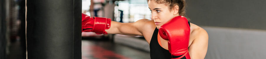 woman punching a heavy bag with gloves on