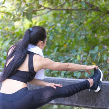 woman stretching out in the park before running