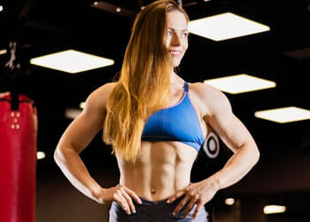woman in a gym showing off her abs
