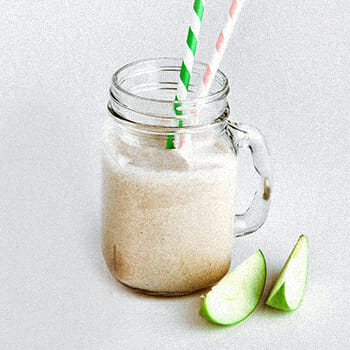 Apple vanilla smoothie on a glass mug with a slice of apple on its side