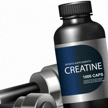 A bottle of Creatine with dumb bells on its side