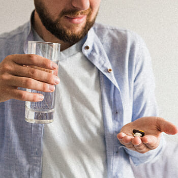 A man looking at the vitamin he's about to take