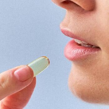 Woman about to take a vitamin