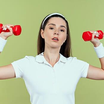 A woman lifting a small dumb bells