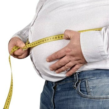 A guy measuring his stomach with a measuring tape