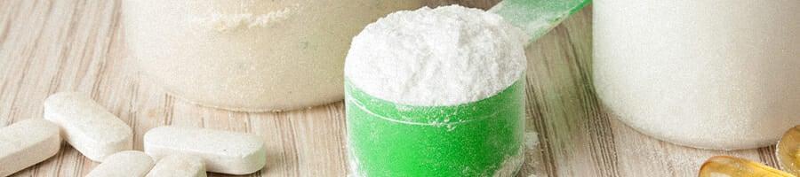 Scoop of creatine and supplements surrounding it