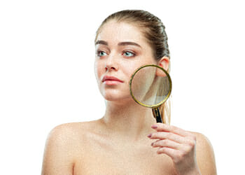 Woman holding a magnifying glass to show her skin