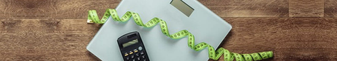calculator and measuring tape on a weighing scale