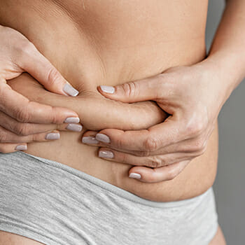 A woman squeezing her body fats