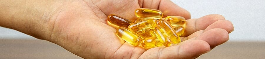 A hand holding a plenty of fish oil supplement