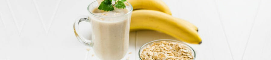 jar filled with banana smoothie and a bowl of oats on the side