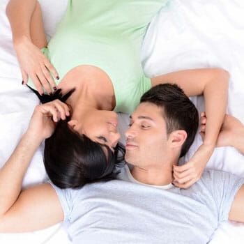 couple in bed staring at each other