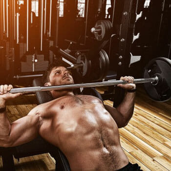 shirtless man using a barbell in a bench