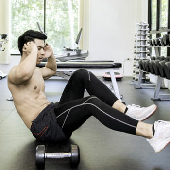 shirtless man doing ab exercises in a gym