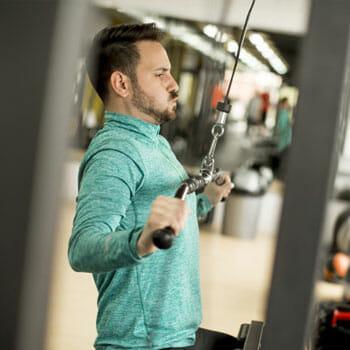 man using a lat machine inside a gym