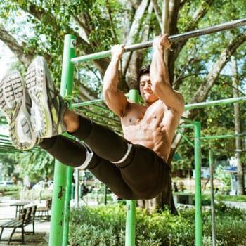 shirtless man using a bar at a park to do pullups